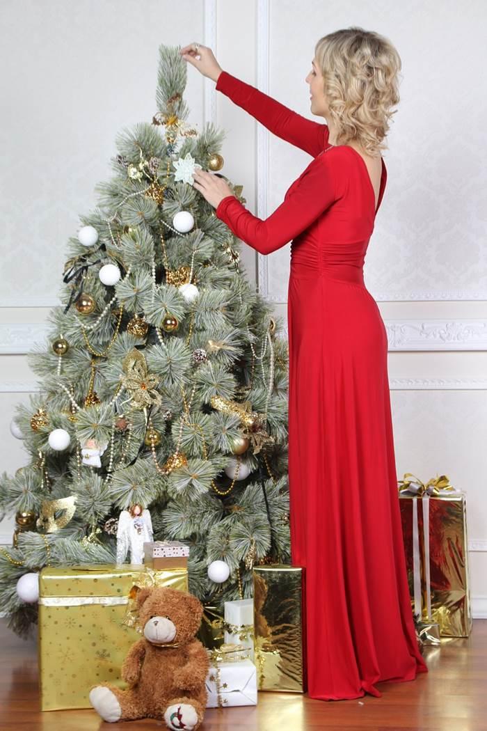 Девушка наряжает новогоднюю ёлку
